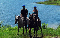 Ride horses along the shore of Lake Arenal