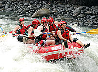 White water rafting surrounded by rainforest-covered mountains